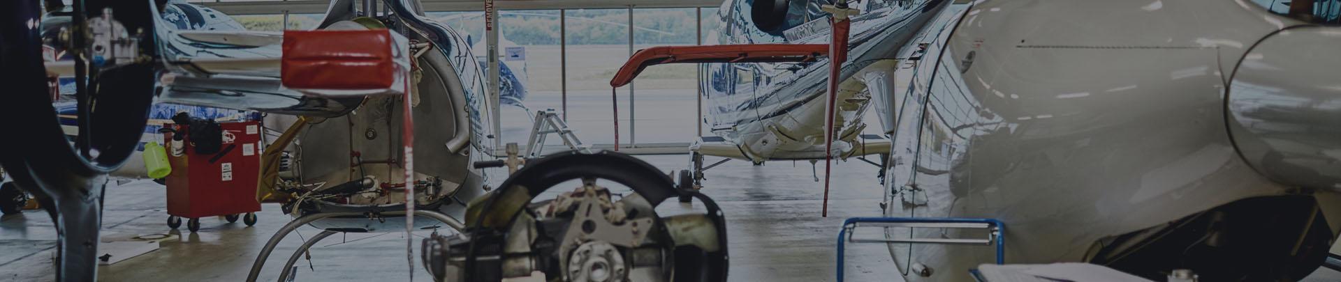 helikoptery stojące w hangarze - baner